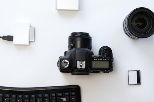 Escritorio blanco con una cámara profesional y accesorios