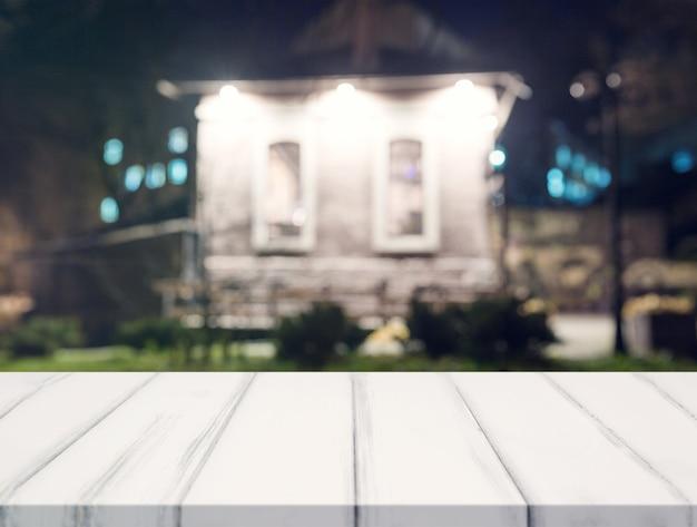 Escritorio blanco frente a la casa borrosa en la noche