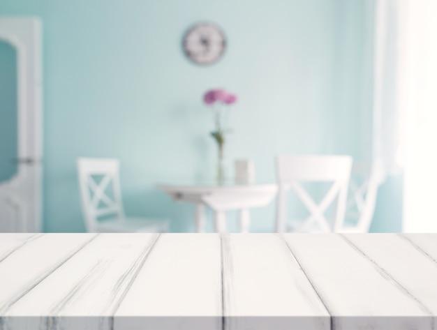 Escritorio blanco frente a la mesa de comedor borrosa contra la pared