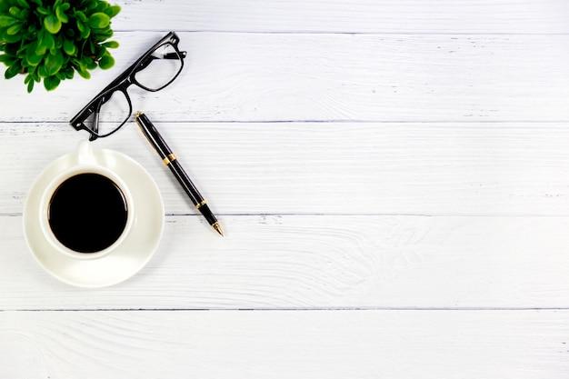 Escritorio blanco de madera con café.