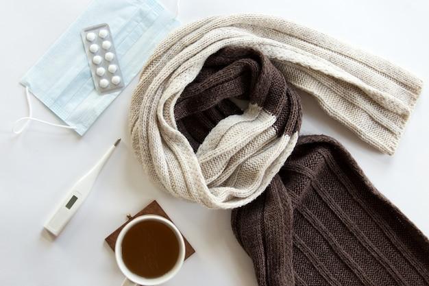 Escritorio blanco con píldoras, termómetro, bebida caliente y una bufanda en él