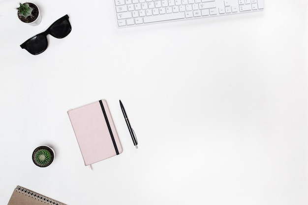 Escritorio de blogger con teclado blanco, teléfono inteligente, cactus y agenda rosa
