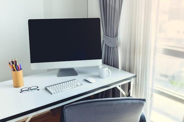 Escritorio de computadora en blanco con teclado, agenda y otros accesorios en mesa blanca