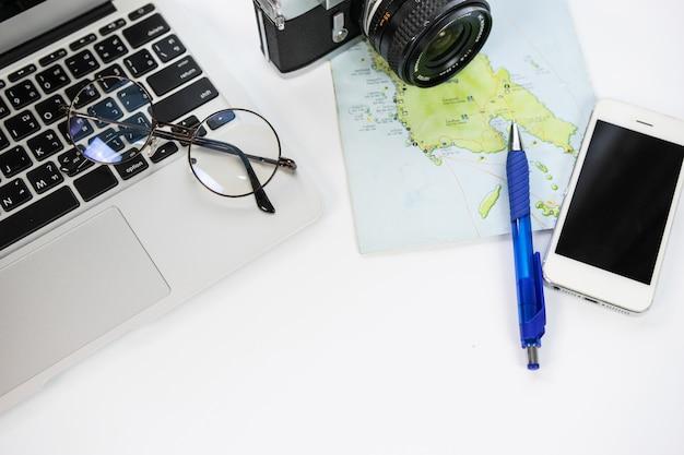 Escritorio con una computadora portátil, teléfono, cámara, mapa y planificación de un viaje.