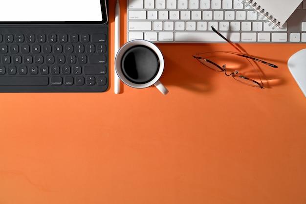 Escritorio creativo de oficina en colores pastel con suministros y espacio de copia.