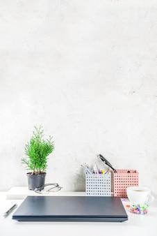 Escritorio creativo de oficina con suministros y taza de café. mesa de oficina blanca con laptop, teclado, cuaderno en blanco, gafas, suministros y taza de café. vista superior del espacio de copia de diseño flatlay