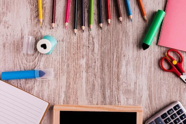 Escritorio creativo con papelería en mesa de madera.