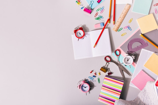 Escritorio cubierto con útiles escolares y coloridos despertadores