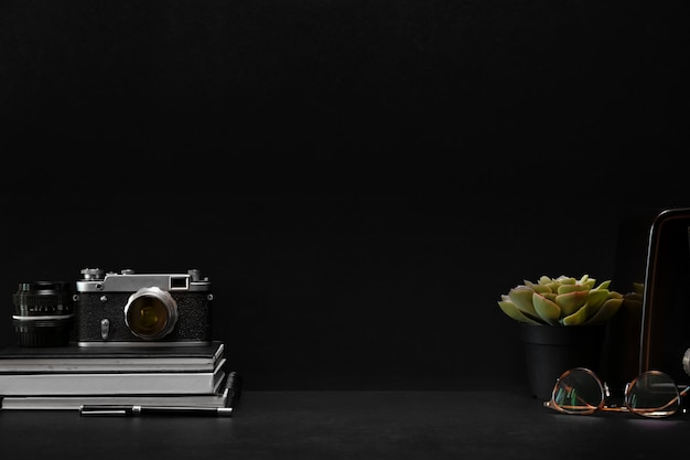 Escritorio de cuero oscuro con cámara vintage, material de oficina y espacio para copiar