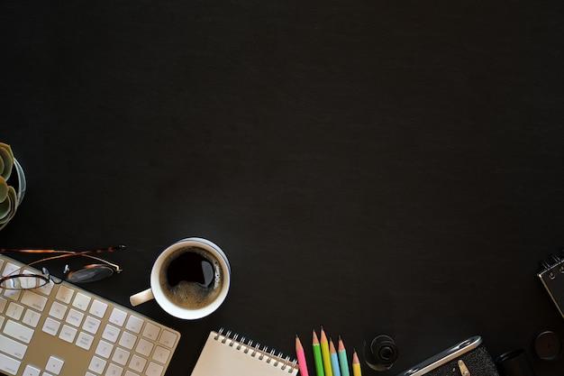 Escritorio de cuero oscuro de oficina con material de oficina y espacio de copia.