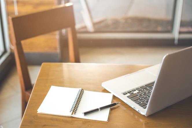 Escritorio de madera y silla con bloc de notas. bolígrafos y laptops