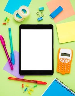 Escritorio desordenado con tableta en blanco