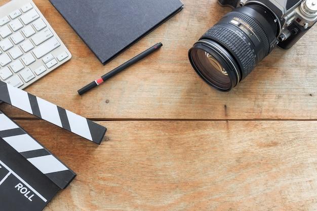 Escritorio del director de cine. tablilla, libro y cámara digital en mesa de madera.