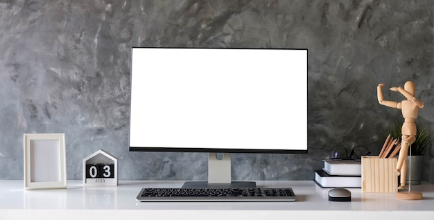 Escritorio de diseñador creativo con pantalla de computadora portátil blanca en blanco con póster de maqueta en el escritorio blanco