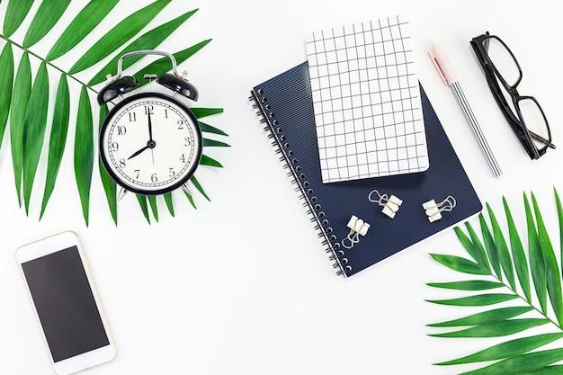 Escritorio de diseño de espacio de trabajo de oficina con alarma, cuaderno, teléfono inteligente, hojas