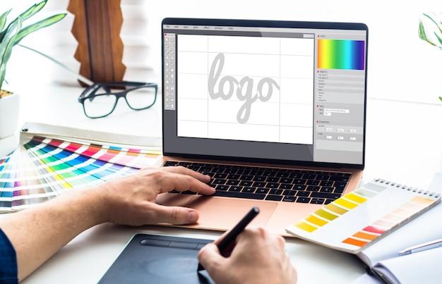 Escritorio de diseño gráfico con laptop y herramientas.