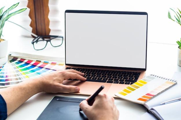 Escritorio de diseño gráfico con maqueta de portátil con pantalla en blanco