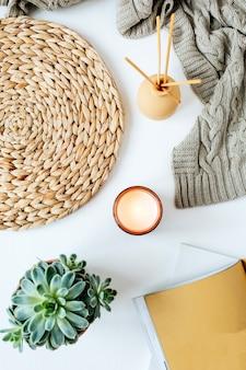Escritorio de espacio de trabajo en casa minimalista moderno de estilo boho con cuaderno, suculentos, cuadros de punto, velas, varillas aromáticas, servilletas de mimbre de paja en blanco