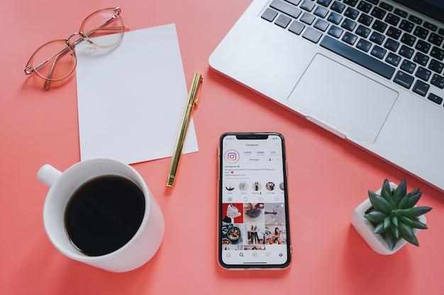 Escritorio de espacio de trabajo plano y teléfono móvil con una aplicación en la pantalla con fondo de computadora portátil y café.