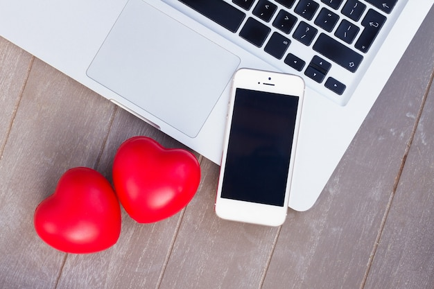 Escritorio de estilo con teléfono moderno, computadora portátil y dos corazones rojos
