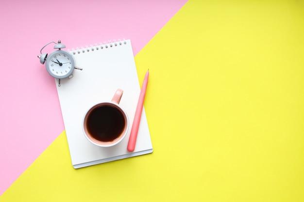 Escritorio para estudiantes con útiles, cuaderno, taza de café, bolígrafo, mini reloj despertador.