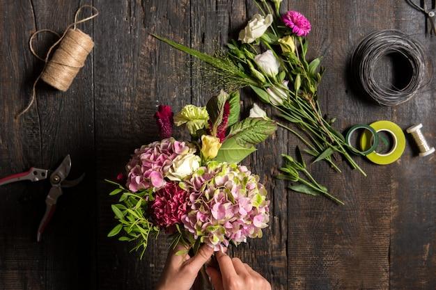 Escritorio de floristería con herramientas de trabajo y cintas