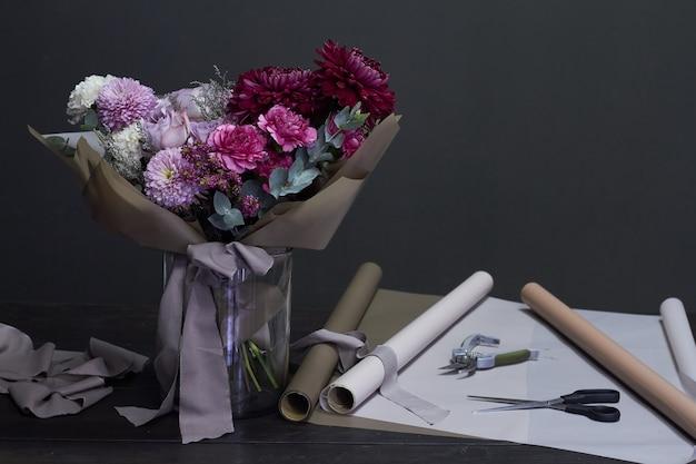 Escritorio de floristería y ramo de tonos púrpura en estilo vintage en un enfoque oscuro y selectivo