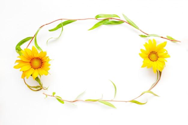 Escritorio de girasol, marco de belleza de verano de ramitas y flores sobre un fondo blanco close-up