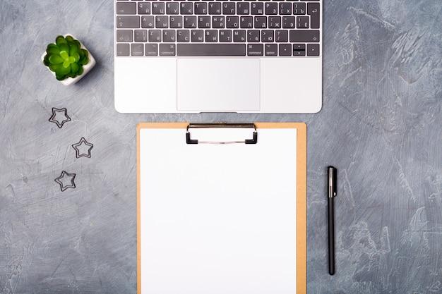 Escritorio gris con computadora portátil plateada y lista de papel en blanco, pluma y planta