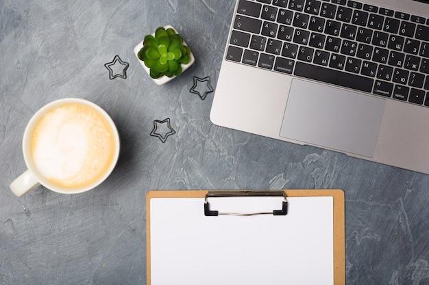 Escritorio gris con computadora portátil plateada y lista de papel en blanco, taza de café y planta