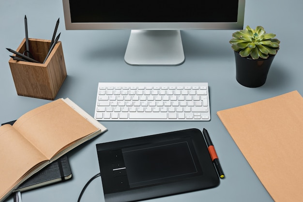 El escritorio gris con laptop, bloc de notas con hoja en blanco, maceta de flores, lápiz y tableta para retocar
