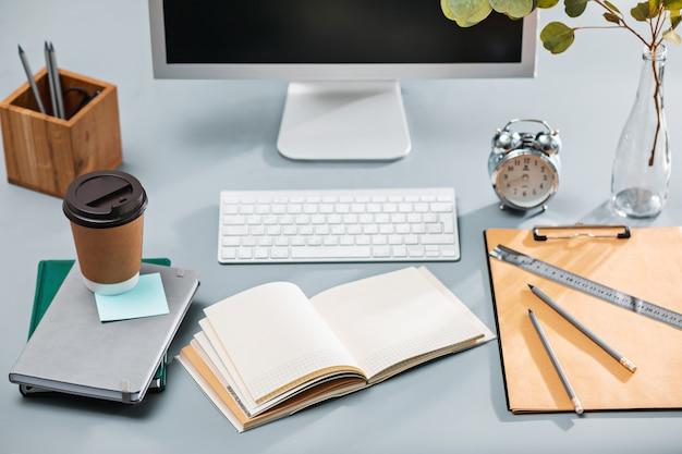 Escritorio gris con laptop, bloc de notas con hoja en blanco, maceta, lápiz y tableta para retocar