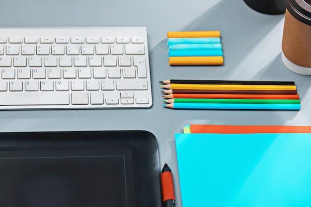 El escritorio gris con laptop, bloc de notas con hoja en blanco, maceta, lápiz y tableta para retocar