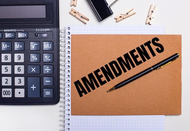 En el escritorio hay una calculadora, un bolígrafo y pinzas para la ropa cerca de un cuaderno con el texto enmiendas. concepto de negocio. vista desde arriba