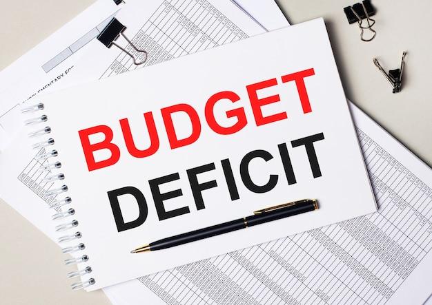 En el escritorio hay documentos, bolígrafo, clips negros y un cuaderno con el texto déficit presupuestario. concepto de negocio