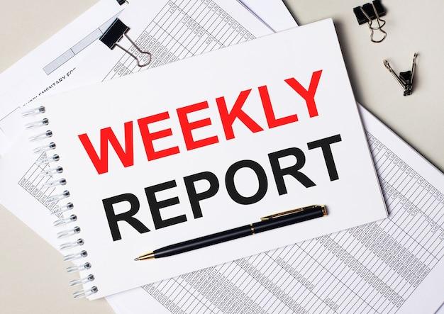 En el escritorio hay documentos, bolígrafo, clips negros y un cuaderno con el texto informe semanal. concepto de negocio