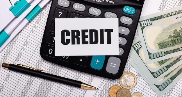En el escritorio hay informes, un bolígrafo, efectivo, una calculadora y una tarjeta con el texto crédito. concepto de negocio