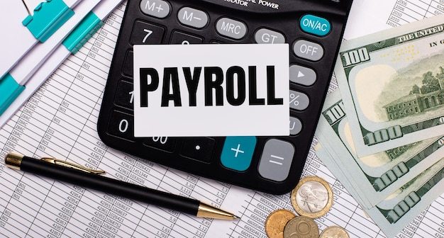 En el escritorio hay informes, un bolígrafo, efectivo, una calculadora y una tarjeta con el texto payroll. concepto de negocio