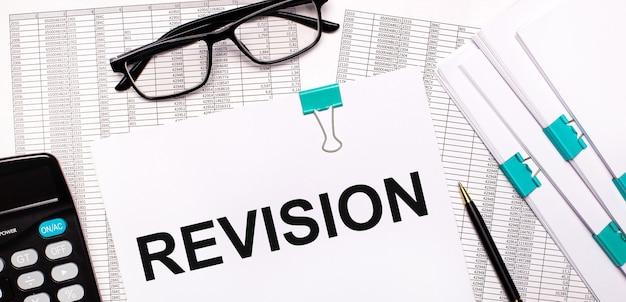 En el escritorio hay informes, documentos, gafas, una calculadora, un bolígrafo y papel con el texto revisión. concepto de negocio