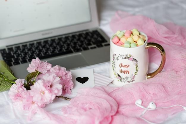 Escritorio con laptop, auriculares y una taza de café con malvaviscos