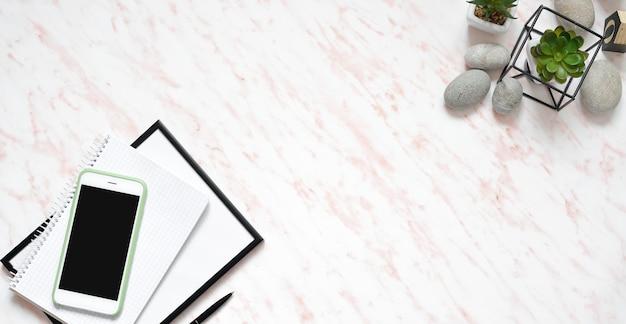 Escritorio largo de mármol plano de office con pantalla plana, teléfono, teclado y notebook