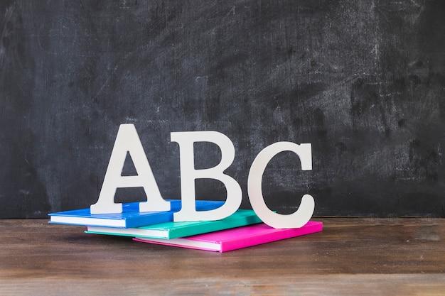 Escritorio con letras abc en libros cerca de la pizarra
