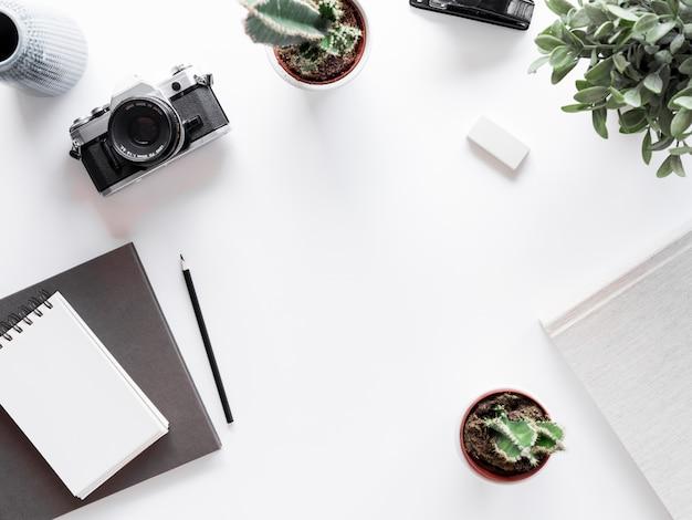 Escritorio con libreta y cámara de fotografías