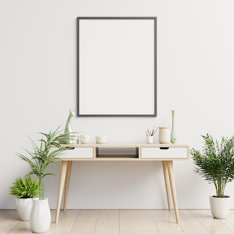 Escritorio limpio y cartel en blanco en la pared blanca