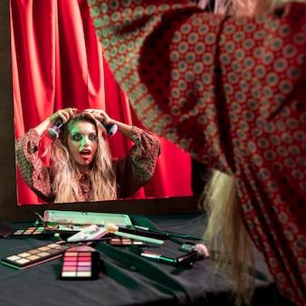 Escritorio lleno de maquillaje y niña mirándose en el espejo