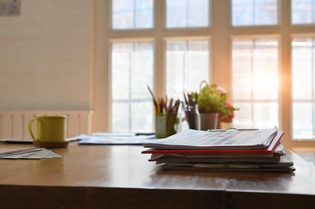 Escritorio de madera creativa con papel de color carta y taza de café.