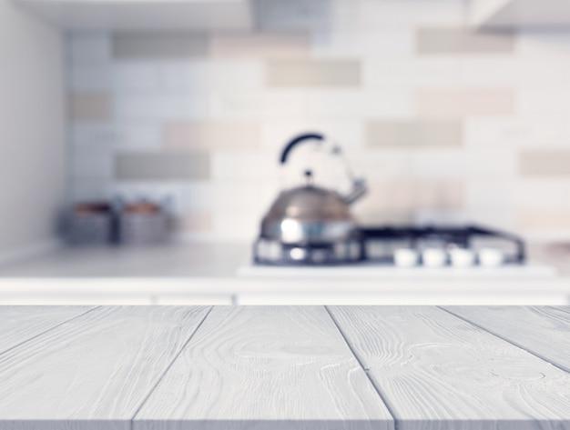 Escritorio de madera en frente del mostrador de la cocina con desenfoque de la estufa de gas moderna
