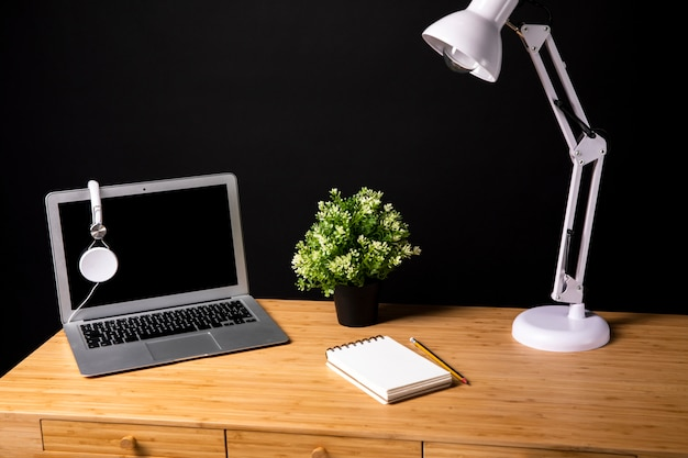 Escritorio de madera con lámpara y laptop.