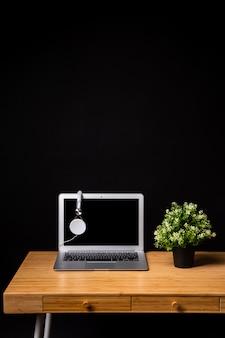 Escritorio de madera con laptop y auriculares.