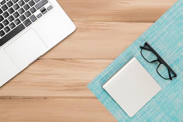Escritorio de madera con laptop y gafas.